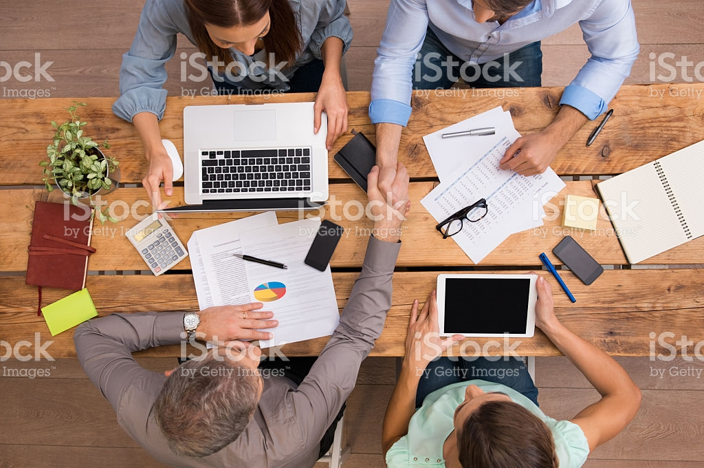 High angle view of businesspeople shaking hands and closing a deal. Successful business teamwork working at the office. Business partners sitting at table and planning work.